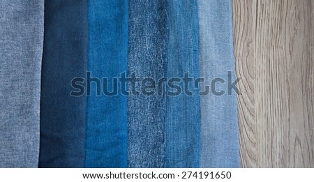 Different shades of blue denim on grey wooden background - stock photo