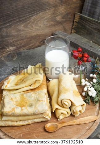 different shapes of pancakes with glass milk, bunch dog-roses as decor, honey on wooden spoon