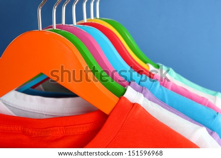 Different shirts on colorful hangers on blue background