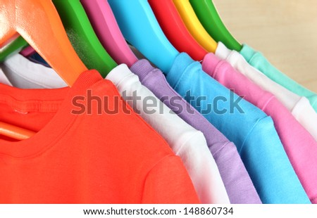Different shirts on colorful hangers on light background