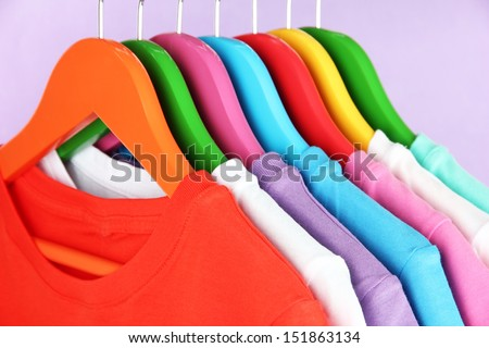 Different shirts on colorful hangers on purple background