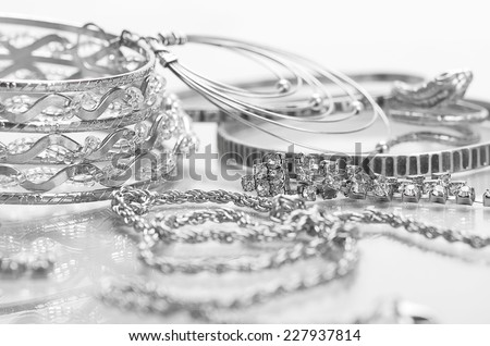 Different silver jewelry on the table. - stock photo