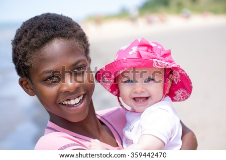 Different Sisters Portrait of two girls of different races, one a baby and one a preteen, embracing in a hug on a sunny beach.  Both smiling with bright eyes and teeth showing. - stock photo