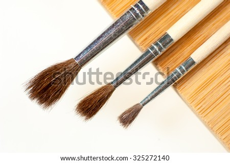 Different size painbrushes isolated on white and wooden background. - stock photo