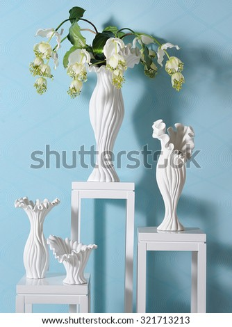 different size vases in a spot of a showroom with beautiful shadows in a blue wall