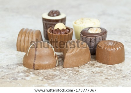 different sizes and shapes of home made chocolate on a tile background