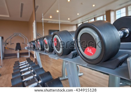 Different sizes and weights dumbbells on stand in modern gym , fitness room - stock photo