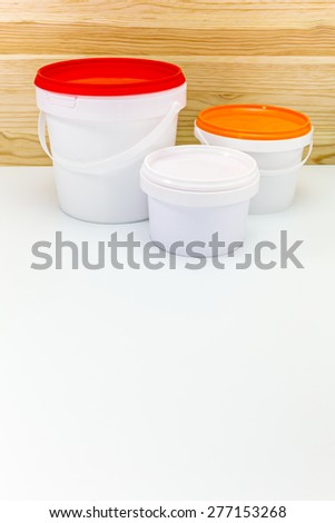 different sizes of paint cans against wooden background - stock photo