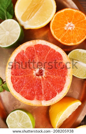 Different sliced juicy citrus fruits, close up