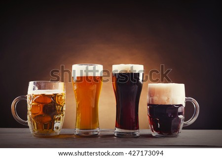 Different sorts of draft beer in glasses on wooden table. Retro stylization - stock photo