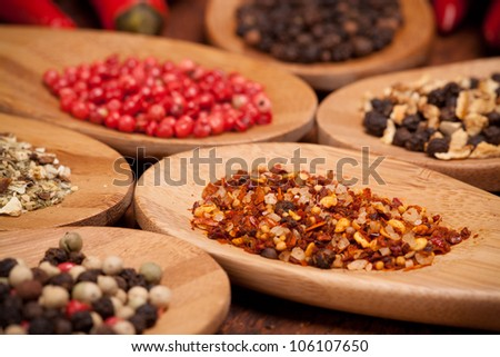 different sorts of pepper in wooden spoons