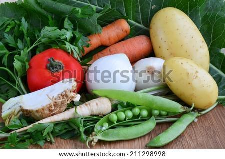 Different sorts of vegetables, tomato, onion, potato, celery, parsley, peas, horseradish, carrots on wooden background - stock photo