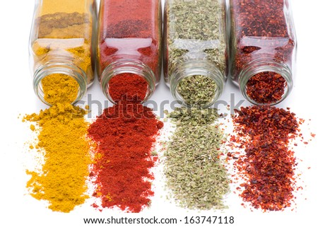 Different spices spilling from spice jars isolated on white background   - stock photo