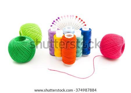 different spools of thread and pins on white
