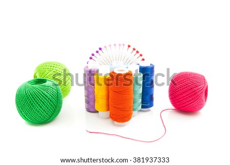 different spools of thread and pins on white background