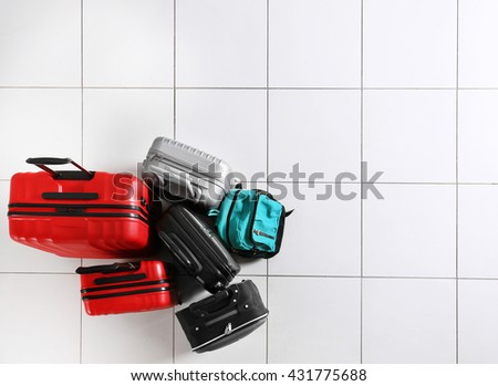 Different suitcases on tile floor, top view - stock photo