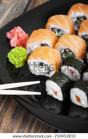 Different sushi rolls,wasabi and ginger on a plate - stock photo