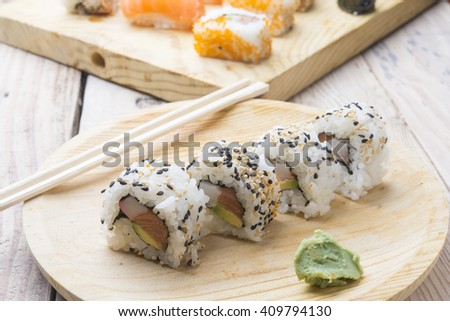 Different Sushi rolls,wasabi and ginger on a plate on wooden bac - stock photo
