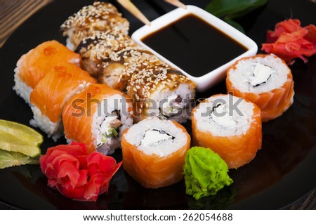 Different Sushi rolls,wasabi and ginger on a plate on wooden background - stock photo