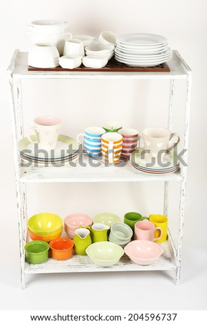 Different tableware on shelves, isolated on white