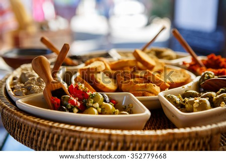 Different tapenade of black and green olives with garlic bread on provencal street market in Provence, France. Selling and buying. Healthy organic local food market. - stock photo