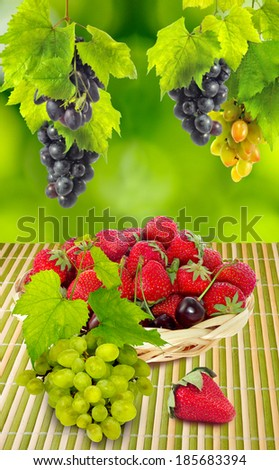 different tasty berries on a green background closeup - stock photo