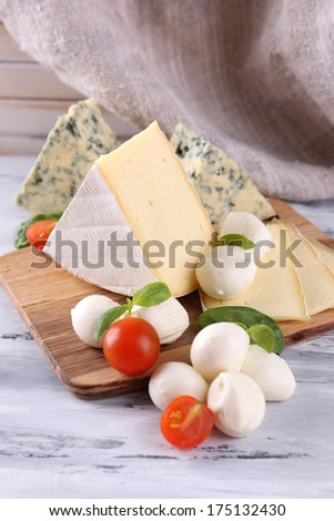 Different tasty cheese, on wooden table