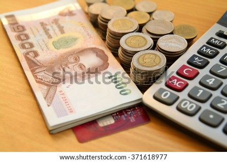 different THB coins and THB banknotes on the background of wood,select focus.
