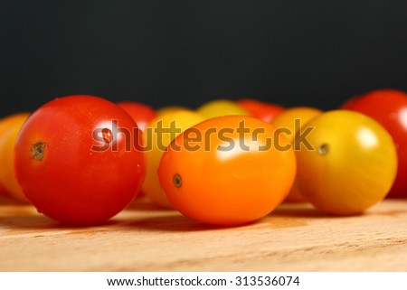 Different tomato cultivars on wooden cutting board. Macro. Black background.