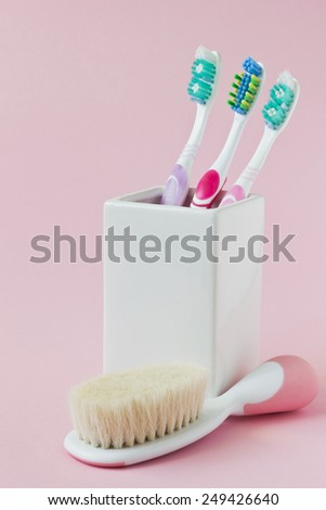 different toothbrushes in a bowl on a colored background. care and hygiene of teeth - stock photo