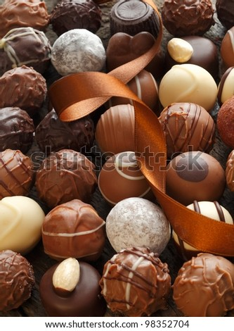 Different Truffles with a brown ribbon as a closeup - stock photo