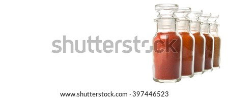 Different type and colors of chilly powder, paprika powder, cayenne powder in glass vial over white background