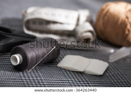 Different types of a tailor's tools on a fabric: needle, scissors, measure, chalk, curl paper - stock photo