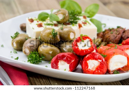 Different types of Antipasto on a plate against wood - stock photo