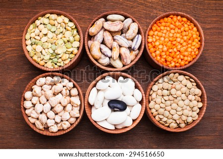 Different types of beans in wooden bowls - stock photo