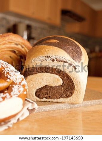 Different types of bread arranged on a chopping board. - stock photo