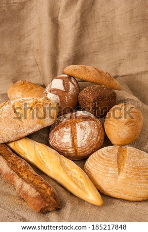 Different types of bread on burlap background