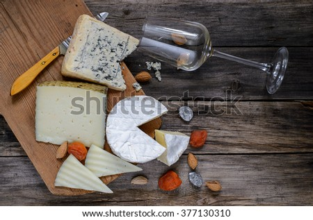Different types of cheese and wine glass on a wooden board.