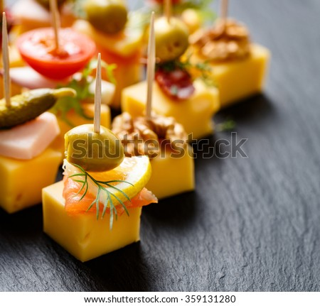 Different types of cheese skewers on a dark background. Delicious appetizers with cheese and various ingredients - stock photo
