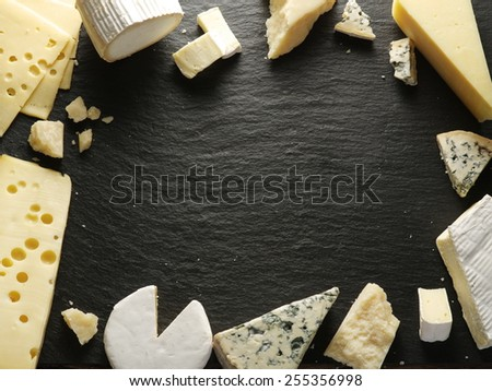 Different types of cheeses arranged as a frame on black board. - stock photo