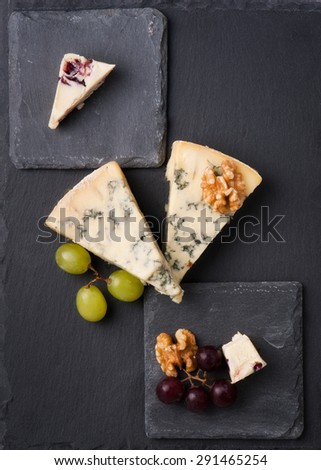Different types of cheeses on black board. - stock photo