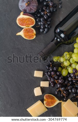 Different types of cheeses, red wine, grapes and figs on black board, top view - stock photo