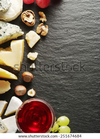 Different types of cheeses with wine glass and fruits. Top view. - stock photo