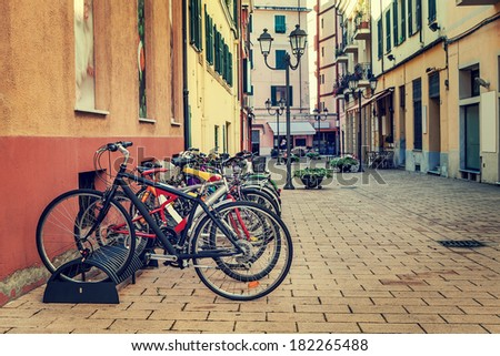 Different types of city bicycles in a row on parking on the street in ventimiglia, Italy. - stock photo