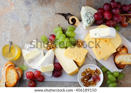 Different types of fresh Cheeses with grapes, honey, bread and walnuts on the slate background. Top view - stock photo