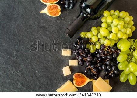 Different types of grapes with bottle of wine, cheese and figs on black background. Top view. - stock photo