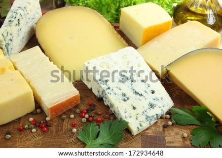 Different types of hard and mold cheeses on a wooden board.