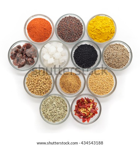 Different types of Indian spices in glass bowls isolated on white background. Top view.
