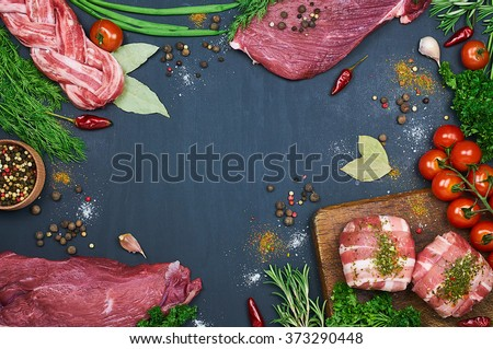 Different types of meat. Fresh butcher cut meat assortment on dark background. Decorated with vegetables and spice. Top view. Close-up - stock photo