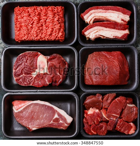 Different types of meat in plastic boxes packaging tray - stock photo